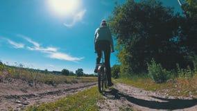 Bicicletta d'annata di guida della giovane donna lungo una strada rurale in un villaggio video d archivio
