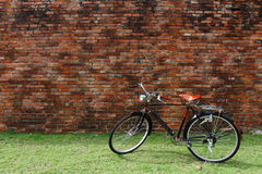 Bicicletta d'annata e muro di mattoni rosso fotografia stock