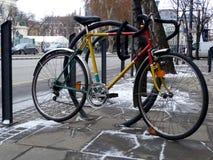 Bicicletta di corsa gialla e rossa chiusa a chiave ad uno scaffale d'acciaio della via con fondo urbano immagini stock libere da diritti