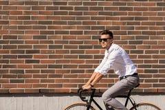 Bicicletta di guida del giovane sulla via della città Immagini Stock Libere da Diritti