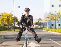 Bicicletta di guida dell'uomo d'affari all'ufficio per ecologico Fotografia Stock