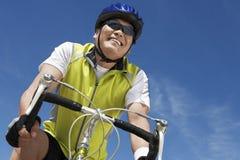 Bicicletta di guida dell'uomo senior contro il cielo Immagine Stock