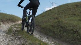 Bicicletta di guida dell'uomo sulla collina dell'erba della montagna stock footage