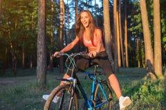 Bicicletta di guida della donna con l'allungamento delle sue gambe nell'aria Immagine Stock Libera da Diritti