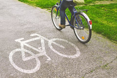 Bicicletta di guida della donna su un percorso della bici Fotografia Stock