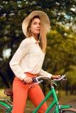 Bicicletta di guida della ragazza in parco fotografia stock