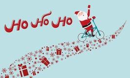 Bicicletta di guida di Santa Claus sul modo del regalo HO-HO-HO Merry Christmas Fotografie Stock Libere da Diritti