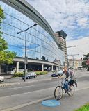 Bicicletta di guida femminile della città con il bambino nella sedia della bicicletta sulla pista ciclabile, contro lo sfondo di  fotografia stock
