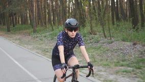 Bicicletta di guida femminile messa a fuoco del pro ciclista nel parco Concetto di addestramento ciclare Movimento lento archivi video