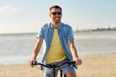 Bicicletta felice di guida dell'uomo lungo la spiaggia di estate Fotografia Stock