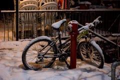 Bicicletta in neve che pende contro l'idrante antincendio Fotografia Stock