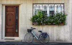Bicicletta parcheggiata davanti alla casa fotografia stock