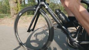 Bicicletta pedaling delle forti gambe del ciclista con le ruote velocemente che filano I muscoli della gamba si chiudono su Conce video d archivio