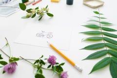 Bicicletta rappresentata nel telaio delle piante verdi con la matita Fotografia Stock Libera da Diritti