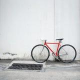 Bicicletta rossa moderna che si appoggia parete bianca Fotografie Stock