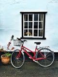 Bicicletta rossa sotto una finestra immagini stock libere da diritti