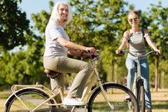 Bicicletta sorridente allegra di guida della donna con la sua nipote dell'adolescente Fotografia Stock