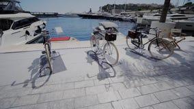Biciclette bianche sulla banchina vicino all'acqua nel Monaco a Monte Carlo video d archivio