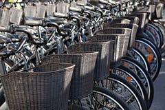 Biciclette con i canestri per la stazione di aggancio di affitto a Copenhaghen, D Fotografie Stock