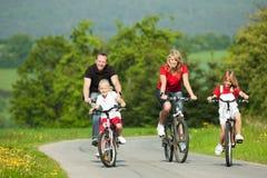 Biciclette di guida della famiglia Immagine Stock