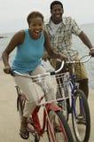 Biciclette di guida delle coppie sulla spiaggia Fotografie Stock