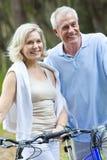 Biciclette di riciclaggio felici delle coppie della donna & dell'uomo maggiore Immagini Stock