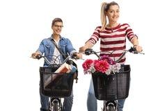 Biciclette di una guida della giovane donna e del giovane Fotografie Stock