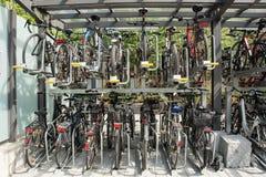 Biciclette parcheggiate accanto ad un edificio per uffici Fotografie Stock