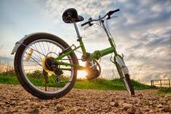 Biciclette parcheggiate su una strada non asfaltata durante il tramonto Immagine Stock Libera da Diritti