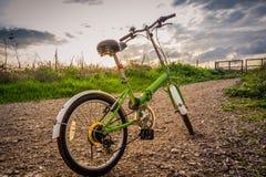 Biciclette parcheggiate su una strada non asfaltata durante il tramonto Immagini Stock Libere da Diritti