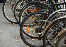 Biciclette parcheggiate sulla via Immagine Stock