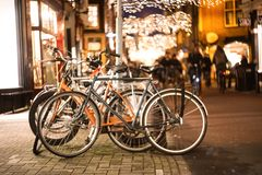 Biciclette parcheggiate, via di notte, stile di vita, bokeh della sfuocatura immagine stock
