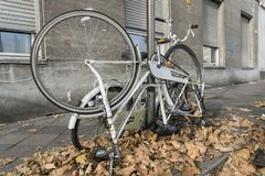 Biciclette rotte legate ad un palo della luce immagine stock