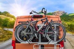 biciclette sul tronco di un furgoncino che passa una strada della montagna immagine stock