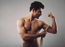 Bicipite di misurazione maschio muscolare immagine stock libera da diritti