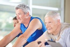 Bicis de giro que montan de la gente mayor en gimnasio Imagenes de archivo