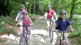 Bicis de montaña del montar a caballo de la familia a lo largo de la pista metrajes