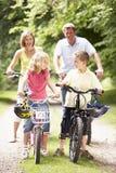 Bicis del montar a caballo de la familia en campo Fotografía de archivo libre de regalías