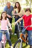 Bicis del montar a caballo de la familia en parque Fotografía de archivo