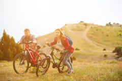 Bicis jovenes del montar a caballo de los pares en las montañas Imagenes de archivo