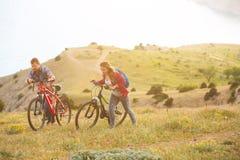 Bicis jovenes del montar a caballo de los pares en las montañas Foto de archivo libre de regalías