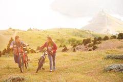 Bicis jovenes del montar a caballo de los pares en las montañas Fotografía de archivo libre de regalías