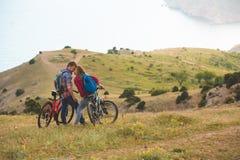 Bicis jovenes del montar a caballo de los pares en las montañas Fotos de archivo