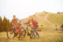 Bicis jovenes del montar a caballo de los pares en las montañas Foto de archivo