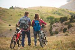 Bicis jovenes del montar a caballo de los pares en las montañas Fotografía de archivo