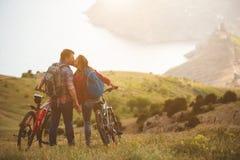 Bicis jovenes del montar a caballo de los pares en las montañas Imagen de archivo