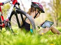 Bicis que completan un ciclo el casco que lleva de la muchacha en sentarse de ciclo cerca de la tableta de la PC de la bicicleta  Imagenes de archivo