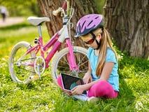 Bicis que completan un ciclo el casco que lleva de la muchacha en sentarse de ciclo cerca de la tableta de la PC de la bicicleta  Imagen de archivo libre de regalías