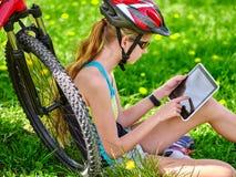 Bicis que completan un ciclo el casco que lleva de la muchacha en sentarse de ciclo cerca de la tableta de la PC de la bicicleta  Foto de archivo libre de regalías