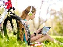 Bicis que completan un ciclo el reloj de las auriculares de la muchacha que lleva en tableta de la PC cerca de la bicicleta Imágenes de archivo libres de regalías